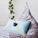 Contrast ric ric and ribbon define this textured cotton cushion, embellished with hand crafted multicolour pom poms and a french floral reverse