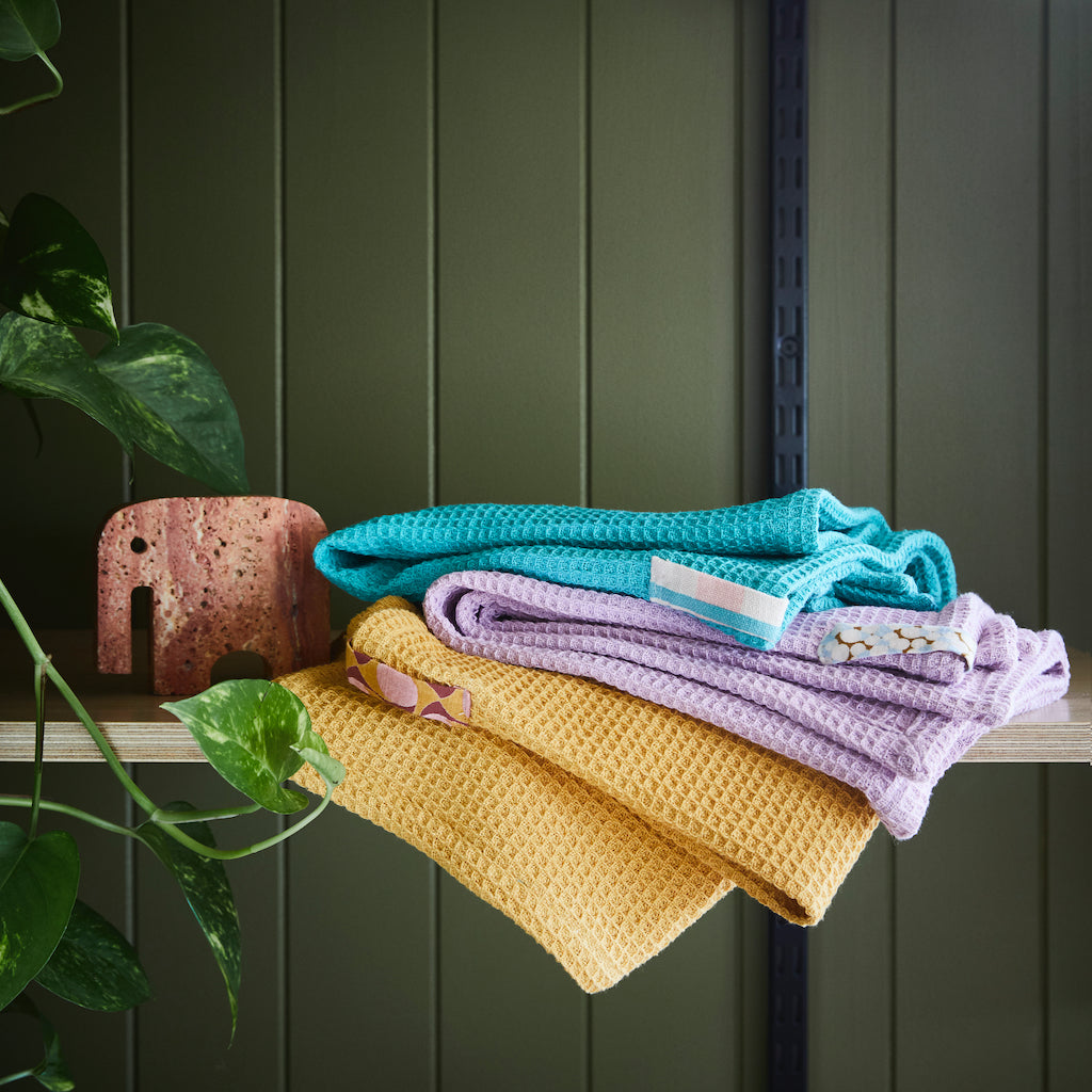 Soft and absorbent textural waffle tea towel in Taffy hue with speckle ribbon loop.