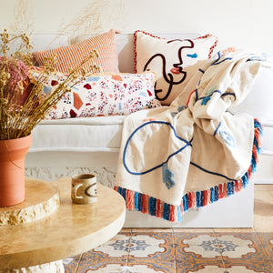 Large parchment throw with hand sewn charms and tufting in blue, orange, blush with multicoloured fringe detail