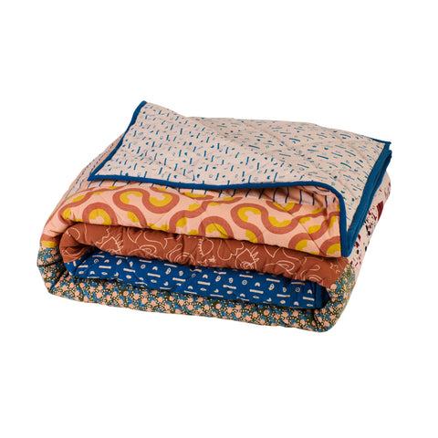 Multicoloured patchwork quilt bedcover with patterned fabric squares and reversible printed side and blue edge piping