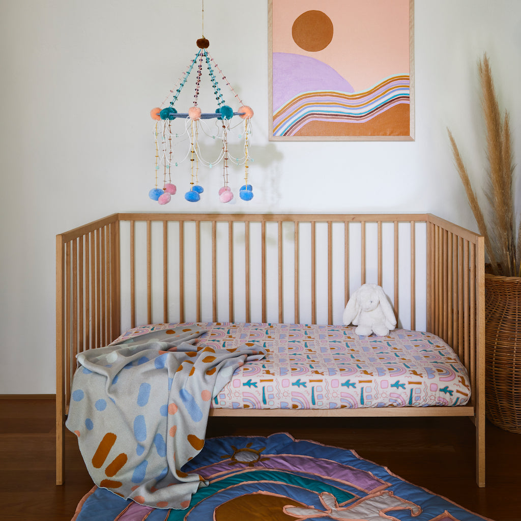 Pickaninny desert cot sheet with child-like illustrations of snakes, cacti and rainbow clusters hand printed on cotton.