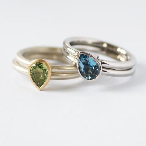 A bespoke and contemporary set of engagement rings in platinum with an aquamarine, and in white and yellow gold with a mint garnet. The inspiration came from seeing this ring