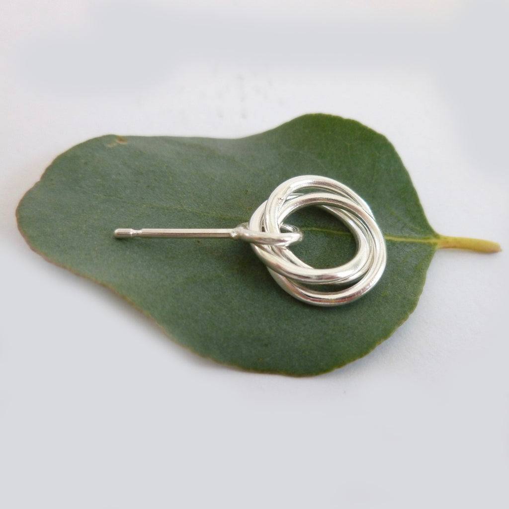 Silver earring on a leaf