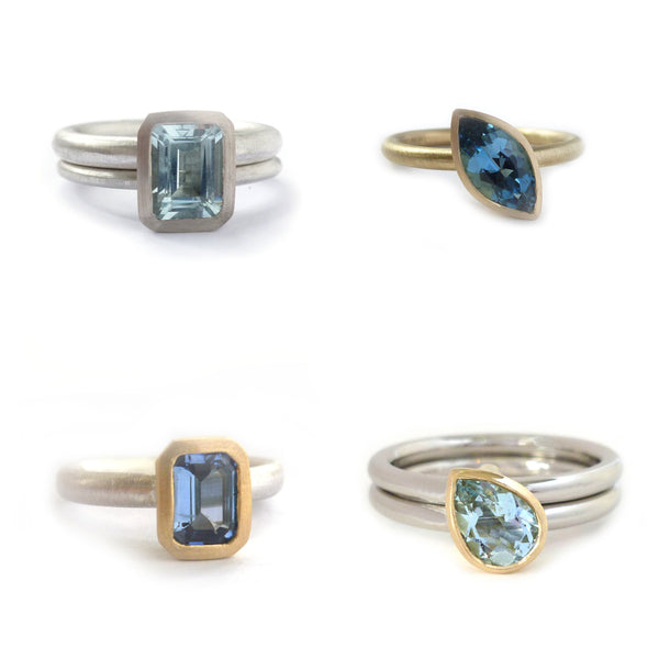 Top left: Silver two band ring with an emerald cut aquamarine in 18k white gold  Top right: 18k yellow gold ring set with a dark blue marquise aquamarine  Bottom left: Silver band with an blue sapphire set into 18k yellow gold  Bottom right: Palladium two band ring set with a pear shape aquamarine in 18k yellow gold