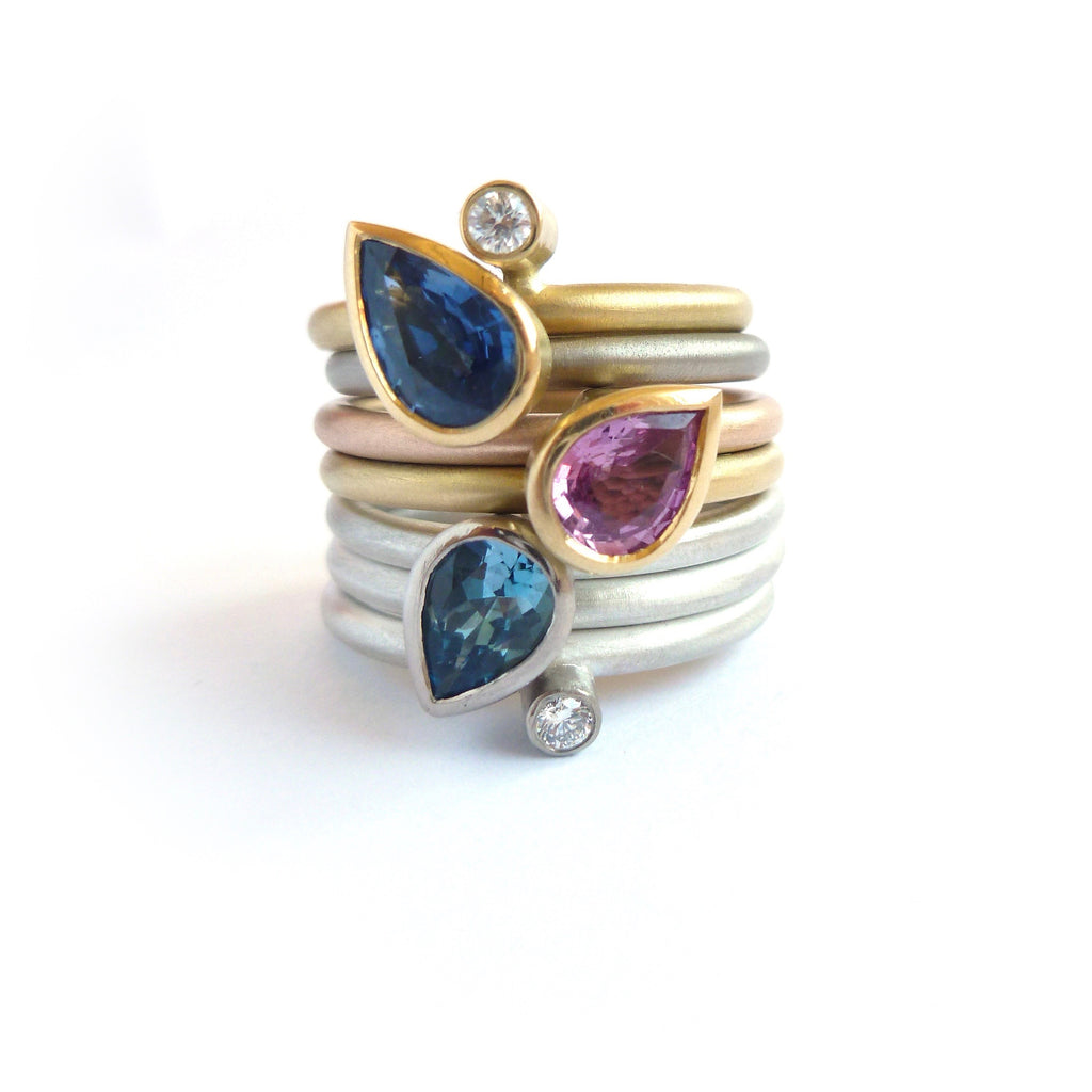 selection of multi band rings by Sue Lane, with diamonds, sapphires, and and aquamarine.