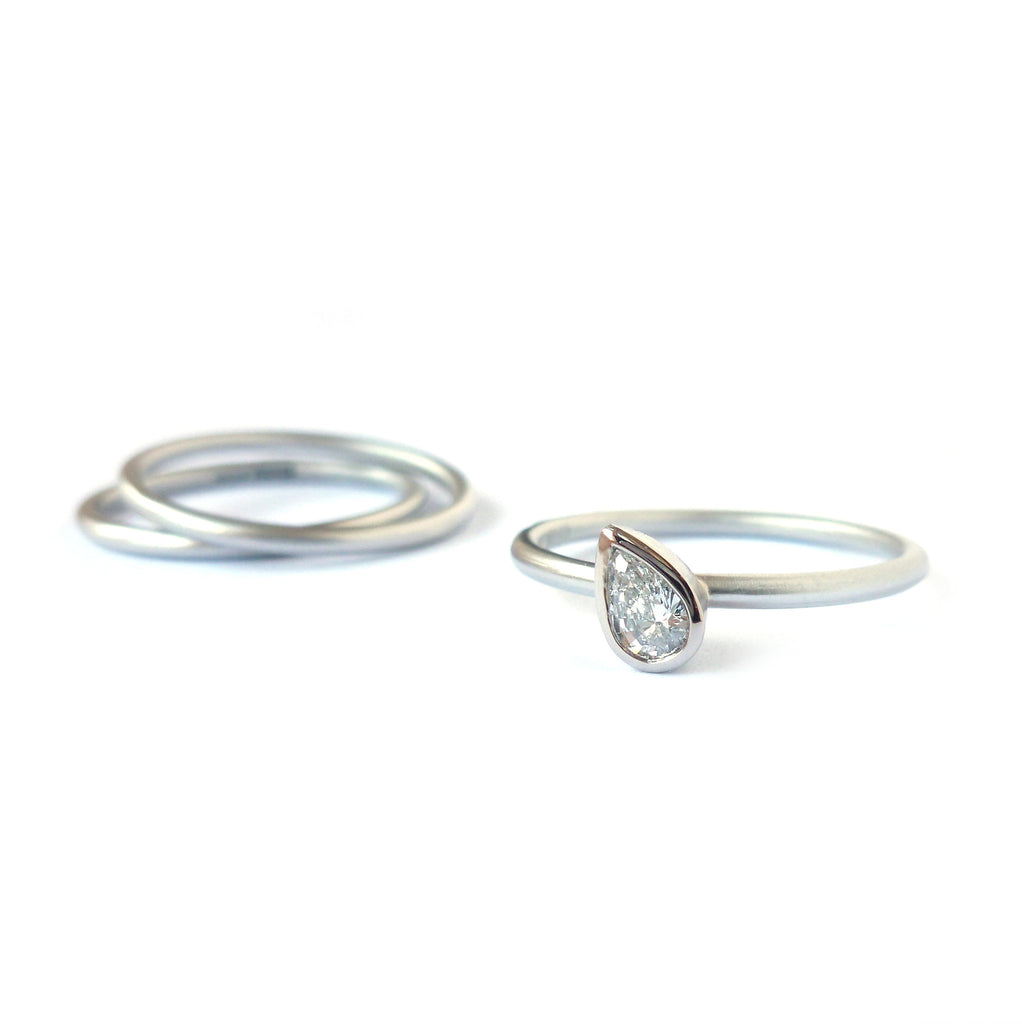 Contemporary, bespoke and modern platinum diamond engagement / wedding stacking ring set, pear shape diamond, matt brushed finish. Handmade by Sue Lane UK