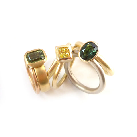 Unique, modern and contemporary two band ring,with a green sapphire. Perfect for a alternative wedding and engagement ring. Handmade in UK by designer Sue Lane.