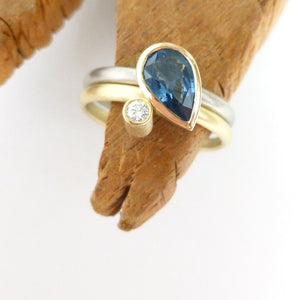 White and yellow gold and cornflower blue pear shape sapphire ring. Multi band ring or interlocking ring, sometimes called double band ring too.