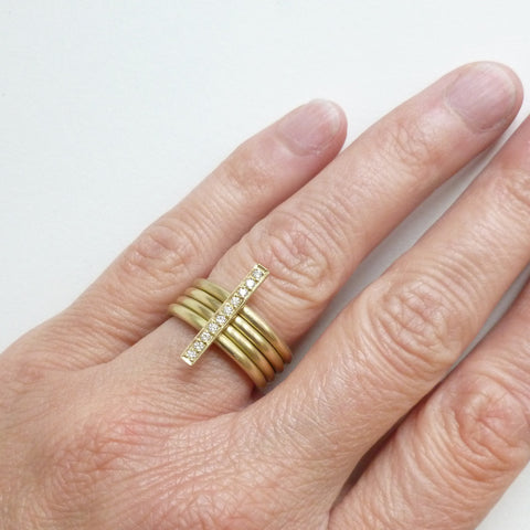 A heavy weight modern four band stacking gold ring with a row of pave diamonds