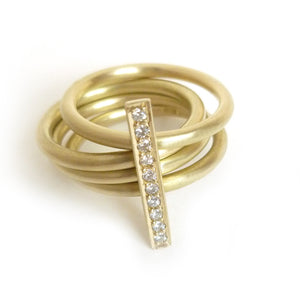 A contemporary heavy weight modern four band stacking gold ring with a row of pave diamonds