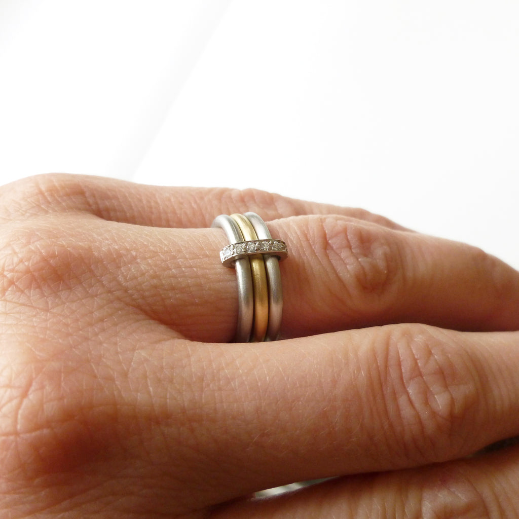 modern two tone, palladium and yellow gold three band eternity ring with diamonds
