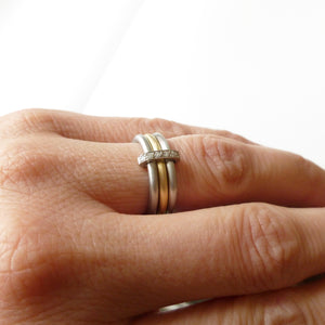 Modern two tone, platinum and yellow gold three band eternity ring with diamonds. Multi band ring or interlocking ring, sometimes called triple band rings too.
