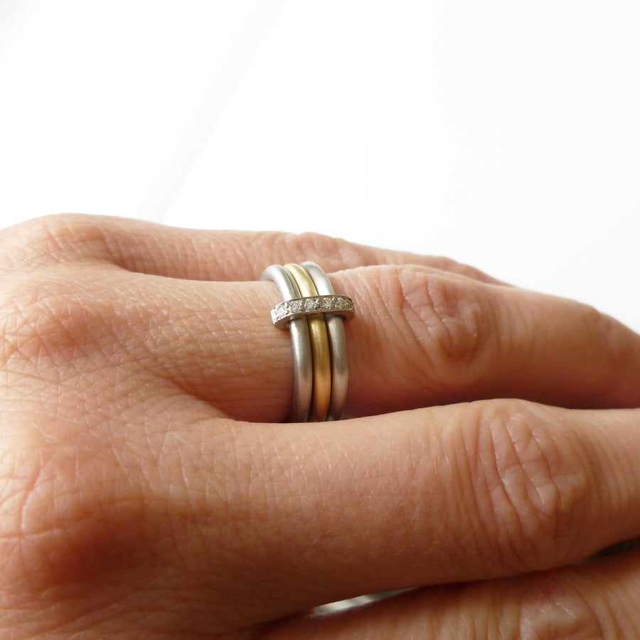 Modern platinum and gold two tone, white and yellow three band ring with diamonds. Multi band ring or interlocking ring, sometimes called triple band rings too.