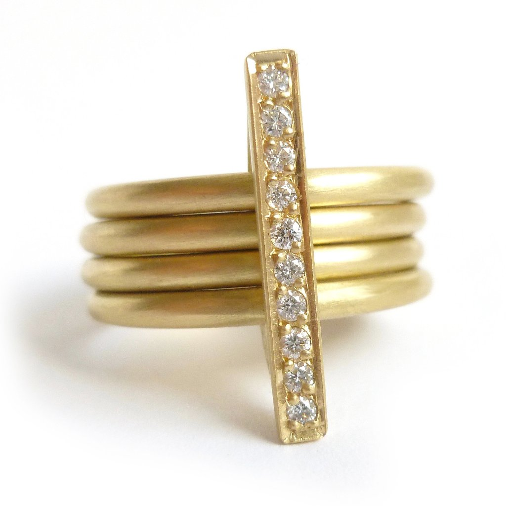 A heavy weight modern four band stacking gold ring with a row of pave diamonds. Multi band ring or interlocking ring.