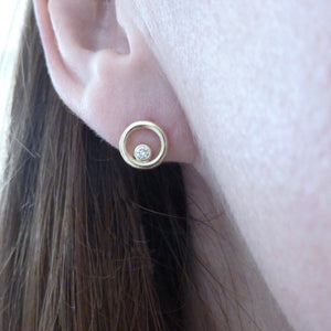 model wearing modern gold and diamond stud earrings