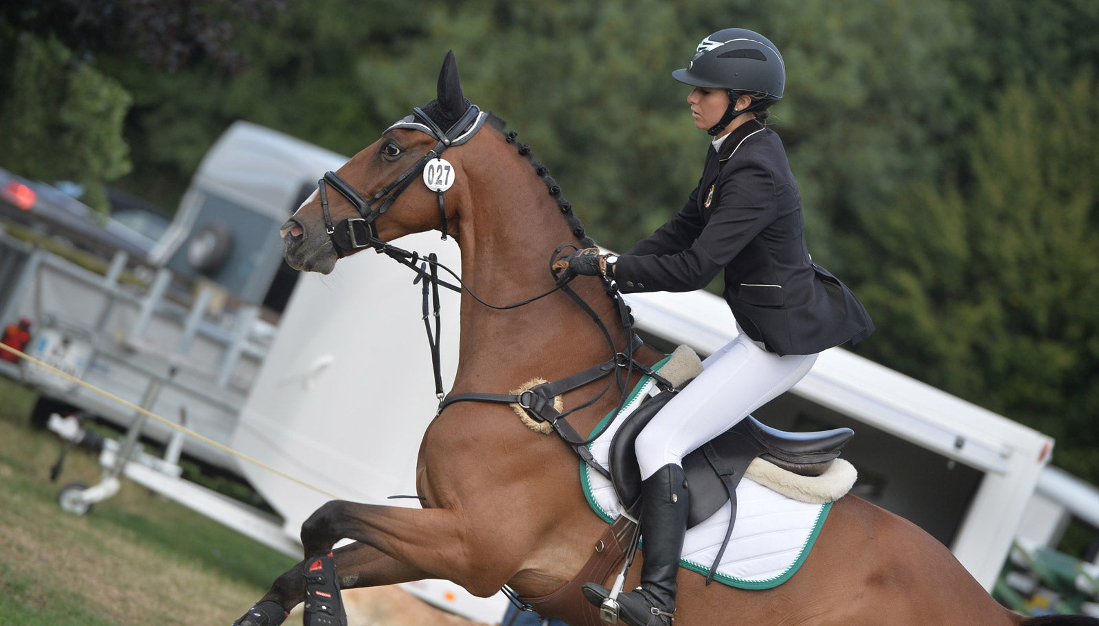 Woman in dressage dress jumping on a horse