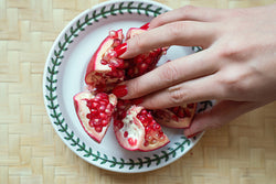 hand in pomegranate seeds on a plate
