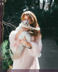 woman in pink holding cat