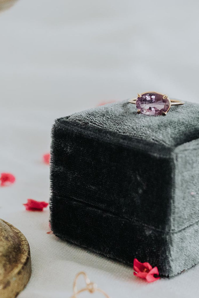 amethyst ring set in gold sitting on a jewelry box