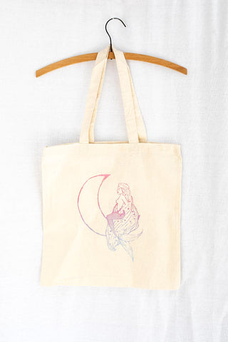 tote bag with mermaid sitting on a crescent moon in a pink to teal color fade