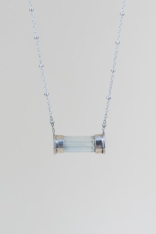 aquamarine crystal with sterling silver capped ends, set horizontally at the end of a satellite chain necklace
