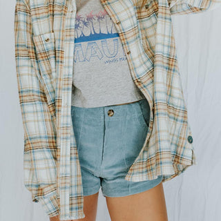 back view of a purple plaid flannel shirt with round crotchet piece in the center
