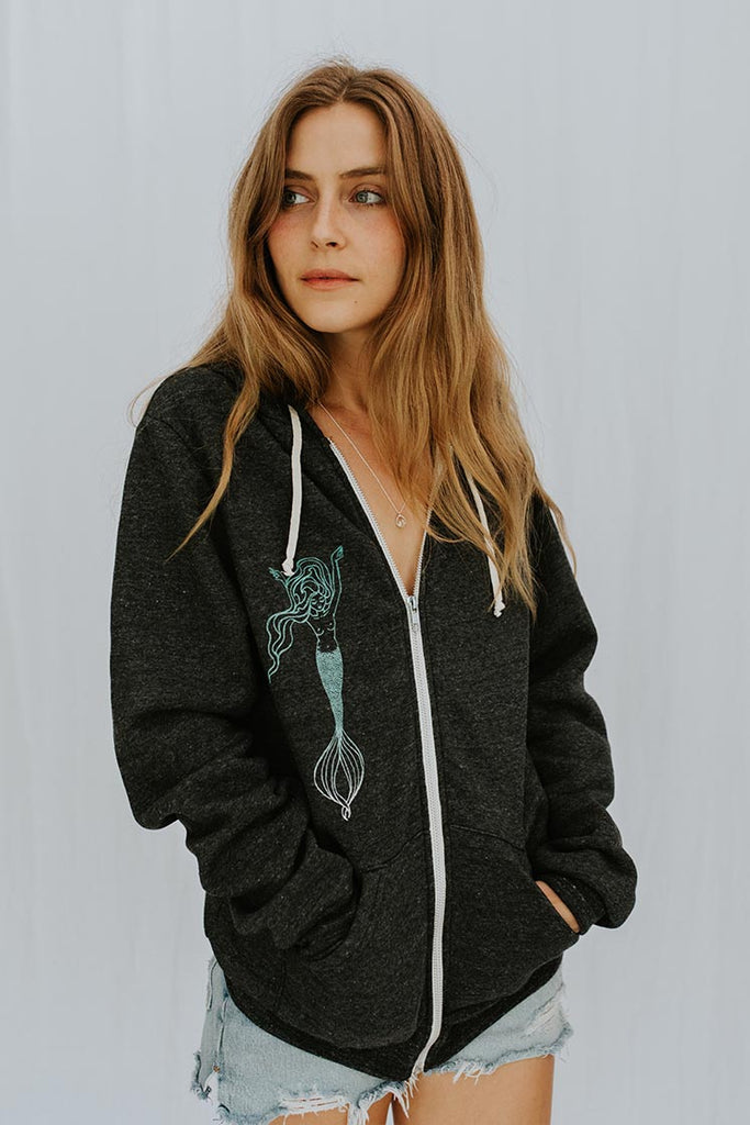 model wearing black zip up hoodie sweater with teal mermaid graphic on right chest