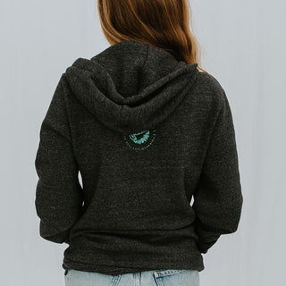 back view of model wearing black hoodie with wings hawaii logo graphic in center