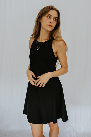 model wearing black ribbed high neck mid length dress