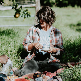 model in a field wearing western shirt, sun tank top and jeans. tea party set up outside on maui