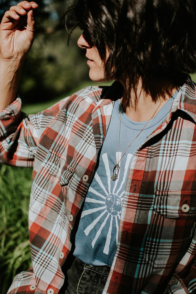 model wearing plaid western shirt, crystal necklace and blue tank top with a sun graphic
