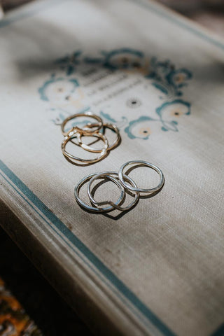 sterling silver and gold filled rings with a v shape sitting on a book