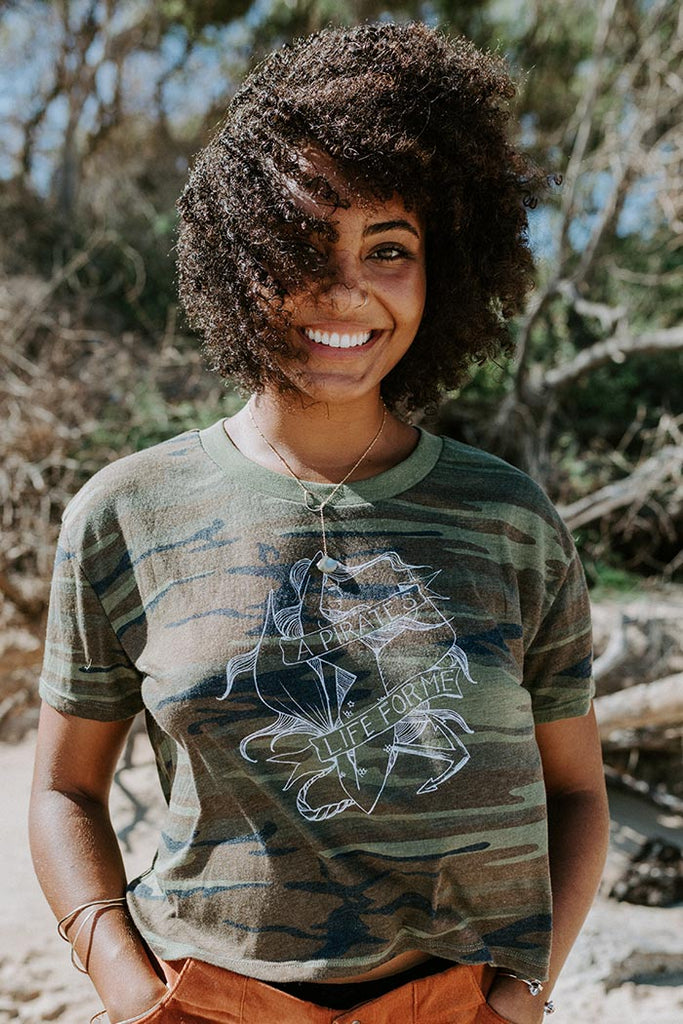 100% cotton camo cropped style women's tee t-shirt with hand drawn graphic a pirate's life for me screen printed on soft casual everyday wear haiku maui wings hawaii green and brown camo mermaid design