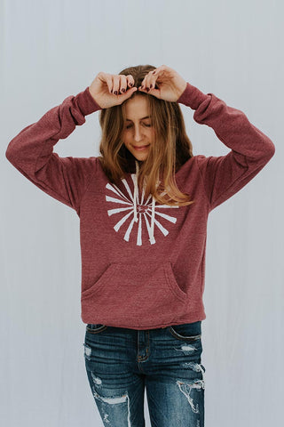 model wearing pullover hoodie in currant red with white sun print