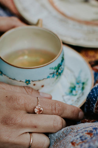 sunstone ring on models hand holding a teacup