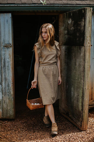 model wearing khaki color flutter sleeve dress standing outside a barn with a basket of eggs