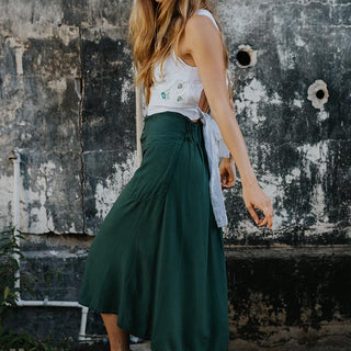 model wearing white top and green long skirt