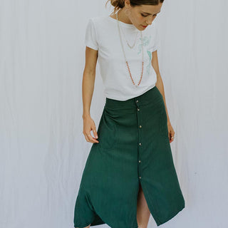 model wearing white tee shirt and long button up green skirt