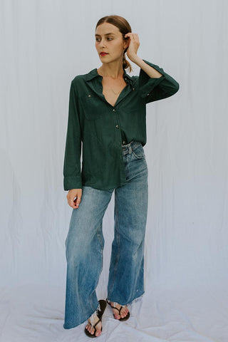model wearing green button up long sleeve blouse with pocket and jeans and sandals