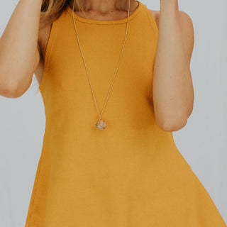 model wearing yellow high neck ribbed tank top and crystal necklace