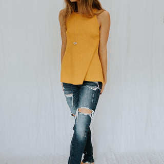 model wearing marigold tank top with crystal necklace and jeans