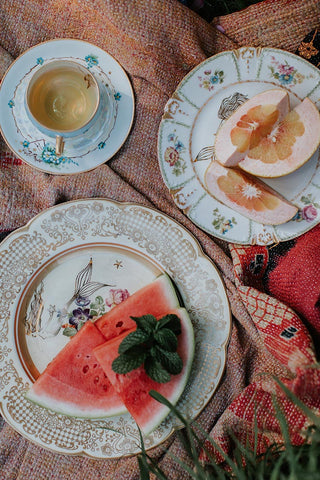 vintage plates with mermaid decals, vintage tea cup and saucer, picnic party with fresh fruit and kantha blanket