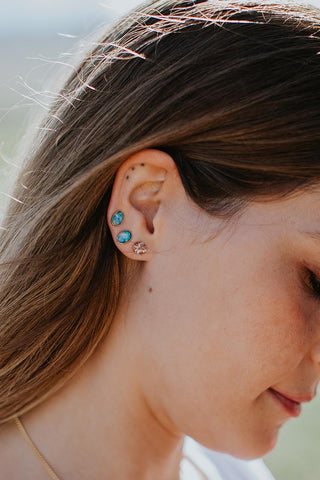 side portrait of a woman wearing small australian opal stud earrings and one crystal stud