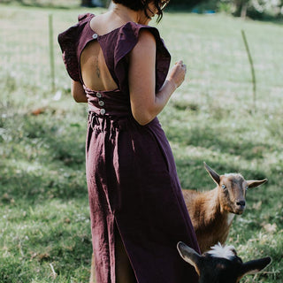 model wearing flutter sleeve top in purple with a cut out hole in the back and matching long skirt plus a hat. she's in a field with two goats