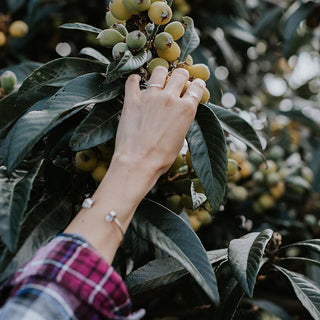 model hand wearing rings and a herkimer cuff bracelet on her arm while reaching for fruit on a tree