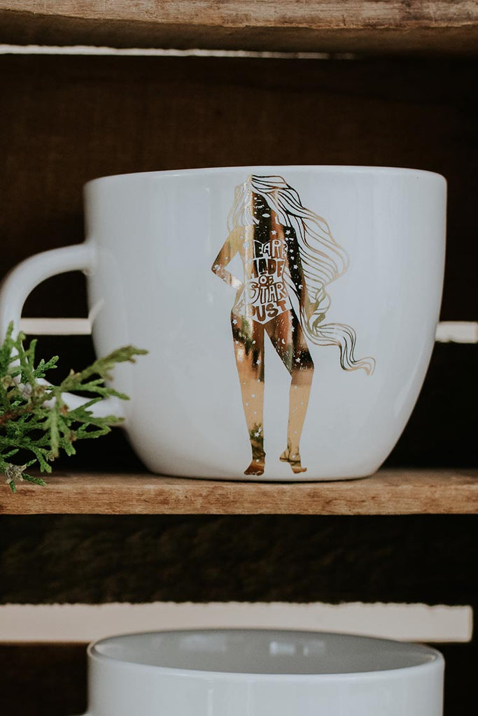 we are made of stardust girl ceramic mug gold and white cosmic celestial vibe wings hawaii