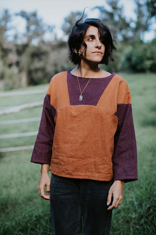 woman in the forest wearing a boxy shape top that has both purple and rust colors with a crystal necklace
