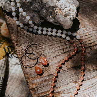flat lay photo of circle hoop earrings with sunstone crystals and a beaded necklace with rhodocrosite and moonstone and herkimer stones on a wooden bench with a large crystal specimen