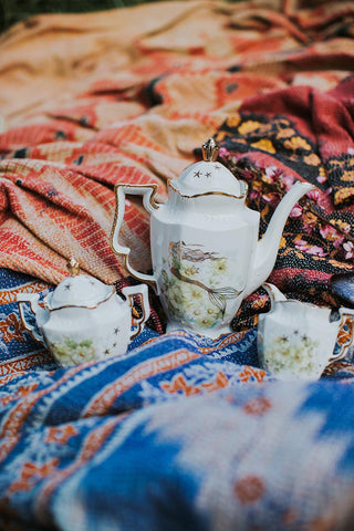 vintage tea pot, creamer and sugar with mermaid decals on vintage kantha blankets