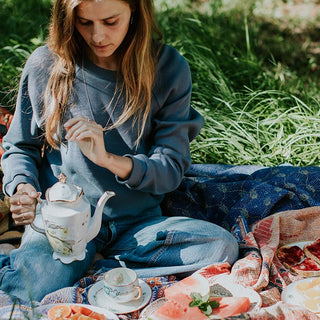 model wearing blue sweater with jeans sitting on a kantha blanket in the jungle having a tea party on maui